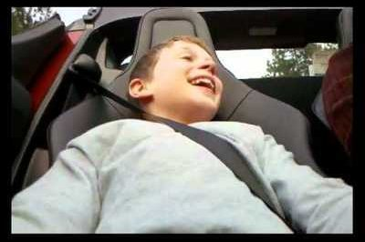 Priceless: Little boy gets his introduction to the world of high-speed cars