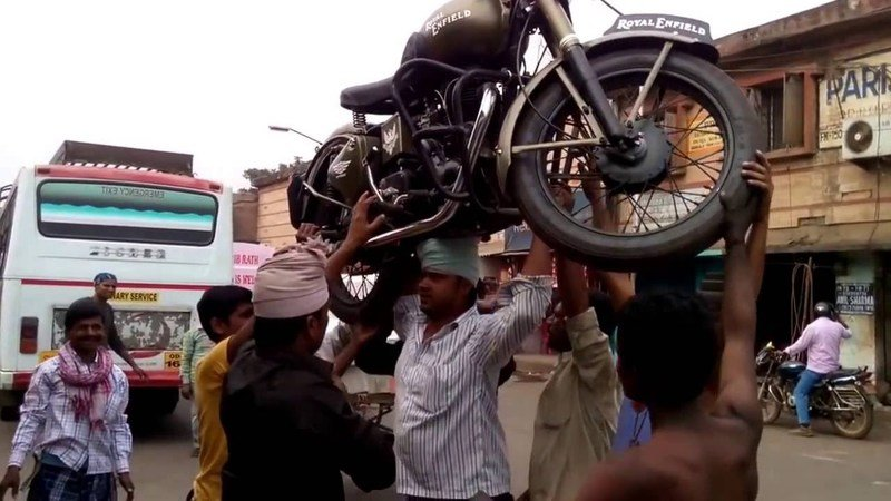 Loading a Royal Enfield onto a bus, carrying it on the head!