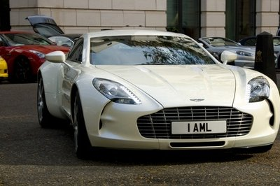 "White Aston Martin One-77 leads a parade of supercars to the ""new"" Silverstone racetrack"
